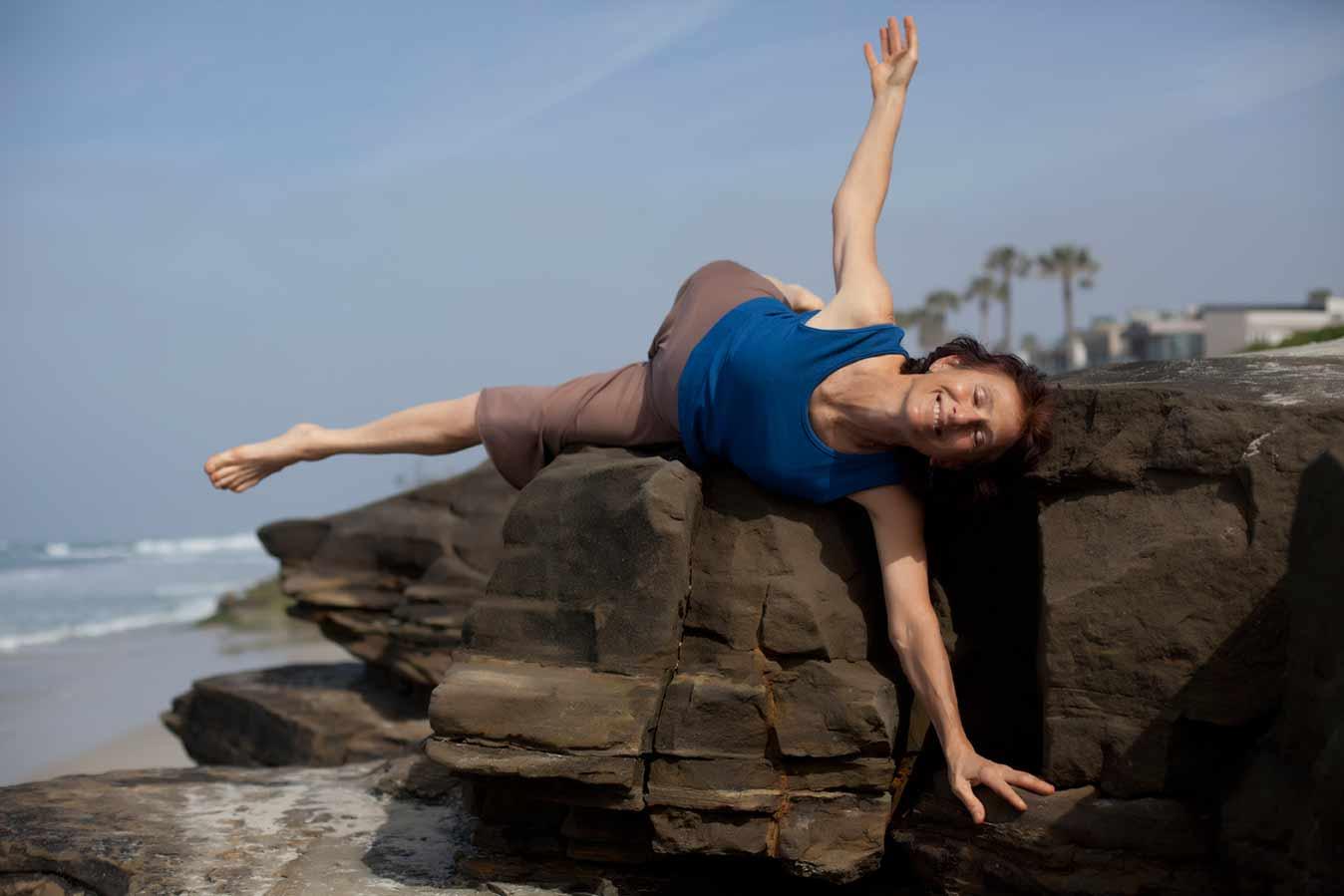 Woman doing yoga on rocks, Zyoga San Diego